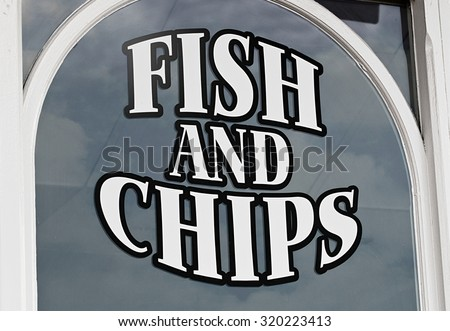 Fish and chips sign painted onto shop window to advertise the popular British Seaside delicacy to tourists - stock photo