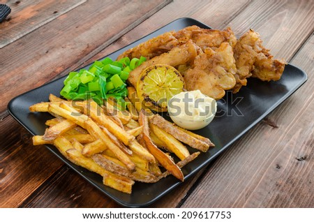 Fish and chips with homemade mayonnaise on black plate - stock photo