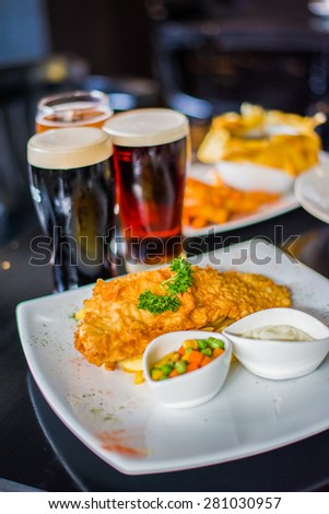 Fish and chips with sauce served with fresh beers - stock photo