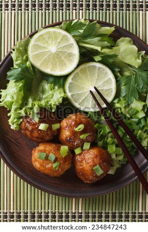 fish balls in curry sauce with lime and fresh herbs and chopsticks on a bamboo table close-up. vertical top view  - stock photo