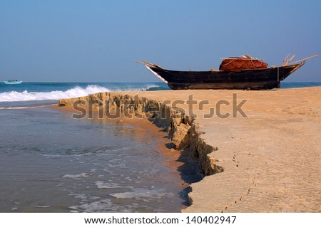 Fish-boat on the shore and holiday cruiser in the Arabian Sea in Goa, India - stock photo