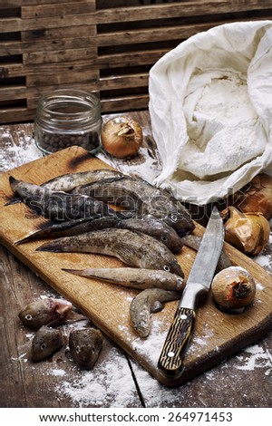 fish breed bull next to the bag of flour on the table wooden table before frying - stock photo