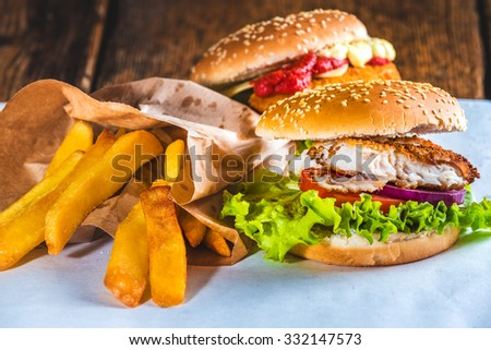 Fish burger with rustic chips on white paper for takeaway - stock photo