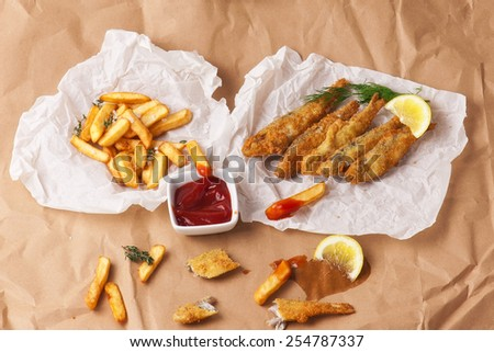 Fish & Chips.Frying sprats  served on the paper. Street food. - stock photo