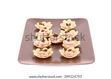 Fish cream and  capers in pastries on brown plate. - stock photo
