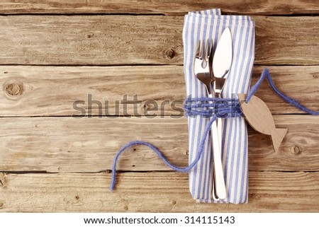 Fish Cutlery Tied on a Purple Napkin with Empty Fish Shaped Tag on Top of a Wooden Table with Copy Space. - stock photo