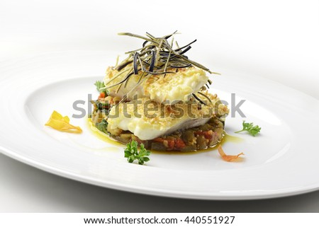 Fish dish, fillet of turbot in almond crust on chopped eggplant and stewed with eggplant chips - stock photo