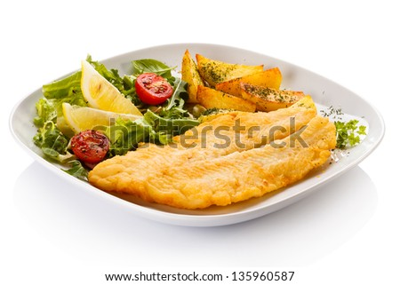 Fish dish - fried fish fillet with baked potatoes and vegetables - stock photo