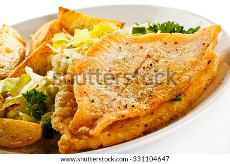 Fish dish - fried fish fillets and vegetables  - stock photo