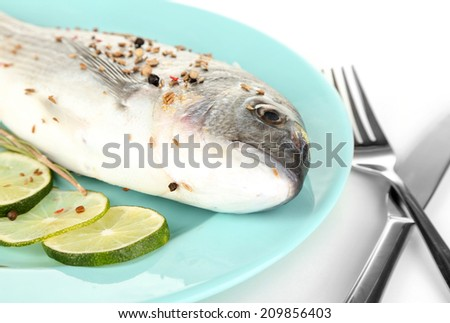 Fish dorado with lemon on plate isolated on white  - stock photo