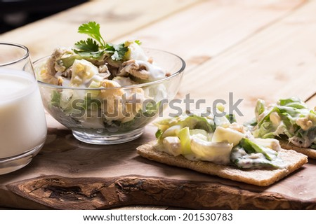 Fish, egg, vegetables salad in the bowl and garlic souse on the wooden table  - stock photo