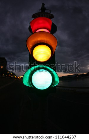 Fish eye photo from a traffic lamp. Photo was taken  at night. All lamps (red, yellow, green) are lighting. - stock photo
