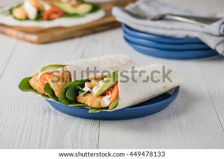 Fish finger wraps with avocado and tomato serves on blue plate  - stock photo