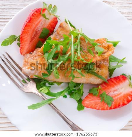 fish fried Arugula and strawberry - stock photo