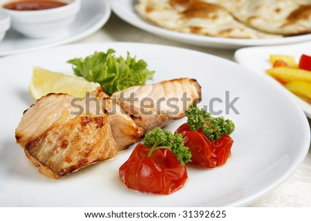 Fish is fried decoration tomato lemon greenery - stock photo