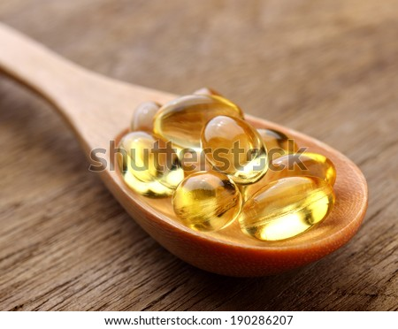 Fish oil capsules in a spoon - stock photo