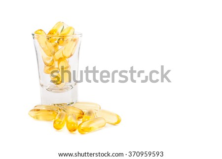 fish oil capsules in glass on white background, with space for text - stock photo