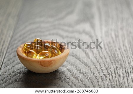 fish oil capsules in wood bowl on wooden table - stock photo