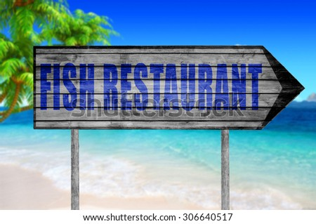 Fish Restaurant wooden sign with on a beach background - stock photo
