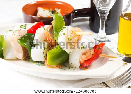 fish skewers  on a white table with oil and wine - stock photo