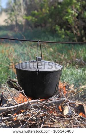 Fish soup preparation in cauldron on bonfire - stock photo