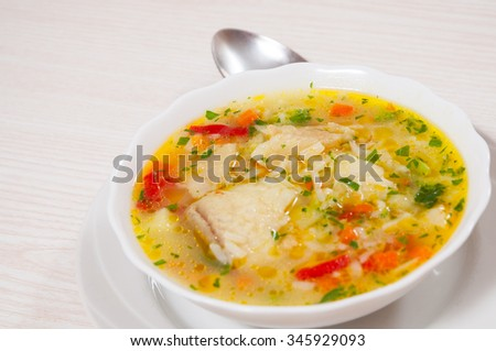 Fish soup with vegetables and rice - stock photo