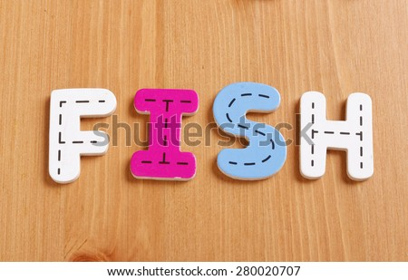 FISH, spell by woody puzzle letters with woody background - stock photo