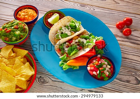 Fish tacos mexican food with guacamole nachos and chili pepper sauce - stock photo