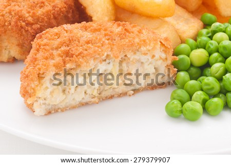 Fishcake made with crumbed fish and potato served with chips and peas - stock photo