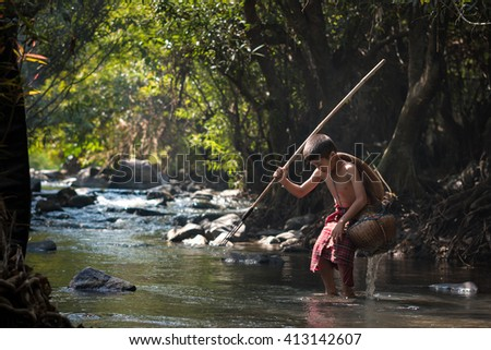 Fisher boy hunter fishing gaff in the waterfall.  - stock photo