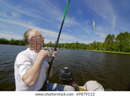 fisher in a boat  holding a spin casting rod and reel and reeling in the line. - stock photo