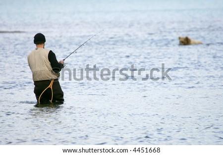 Fisherman and bear fishing for salmon, Katmai National Park, Alaska - stock photo