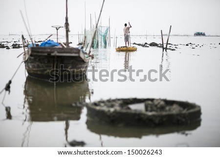 Fisherman and old fishing boat for coastal fisheries. - stock photo