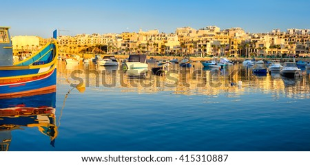 Fisherman and passenger boats in Marsaskala bay in South Malta early in the evening - stock photo