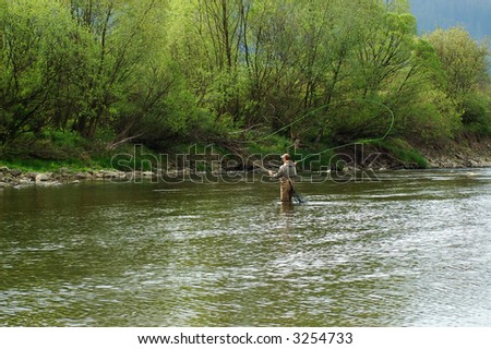 Fisherman angling on the river - stock photo