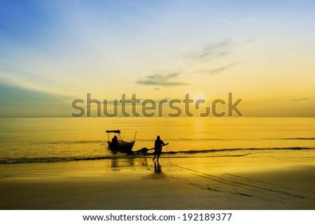 fisherman at beach via great sunset - stock photo