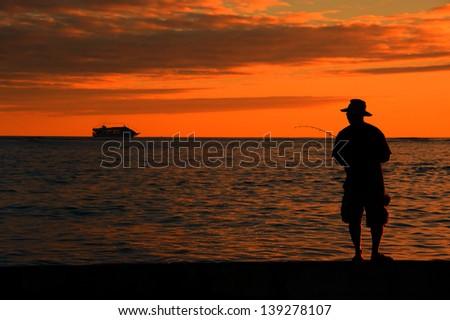 Fisherman at sunset on Waikiki beach, Hawaii - stock photo