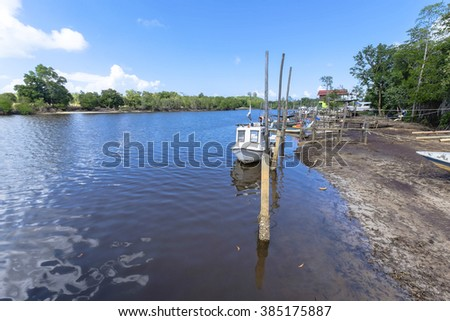 fisherman boat in a jetty with blue sky background - stock photo