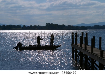 Fisherman, Boat Silhouette at Sunset - stock photo