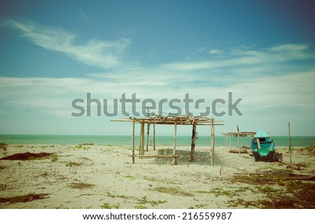 fisherman canoe boat and wooden hut in beautiful tropical deserted beach in the coast of ecuador - stock photo