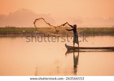 fisherman cast a net on the rowboat at the Taungthaman lake, near by U bein bridge, Amarapura, Myanmar. - stock photo