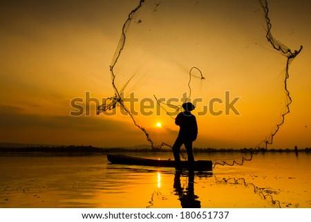 Fisherman casting his net at sunrise - stock photo