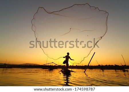 Fisherman casting his net at sunrise on the Mekong River in Thailand. - stock photo