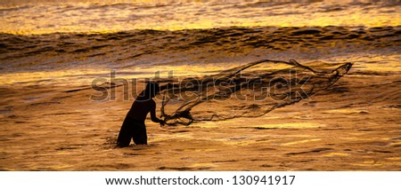 Fisherman casting his net at the sunset in Cerro Azul, Lima, Peru - stock photo