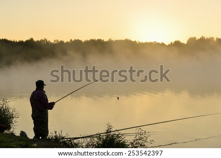 Fisherman catches fish by spinning on the lake at sunset - stock photo