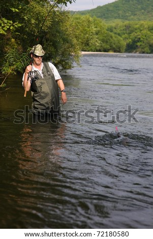 Fisherman catches of salmon (pink salmon) on the river. Early morning. - stock photo