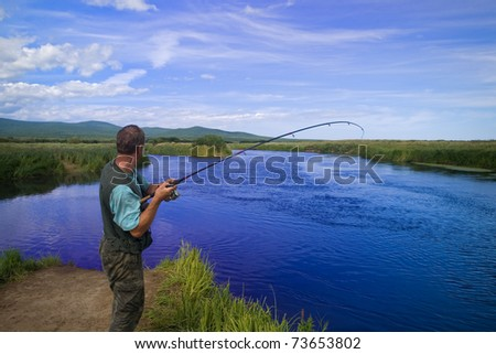 Fisherman catches of salmon (pink salmon) on the river mouth. Photographed through a polarizing filter. - stock photo