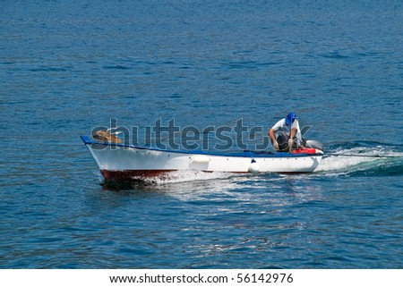 fisherman coming back on his fishing boat - stock photo