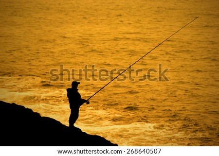 Fisherman fishing a perpon beside the sea. - stock photo