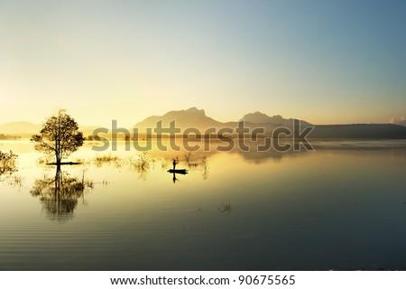 fisherman fishing in big lake ,thailand - stock photo